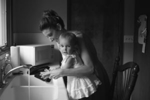 Mother and child washing hands in kitchen sink