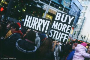 Crowd of people shopping with placards which read Hurry! Buy More Stuff