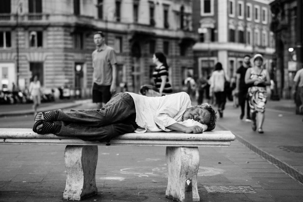 Man asleep on stone bench in a pedestrian precinct