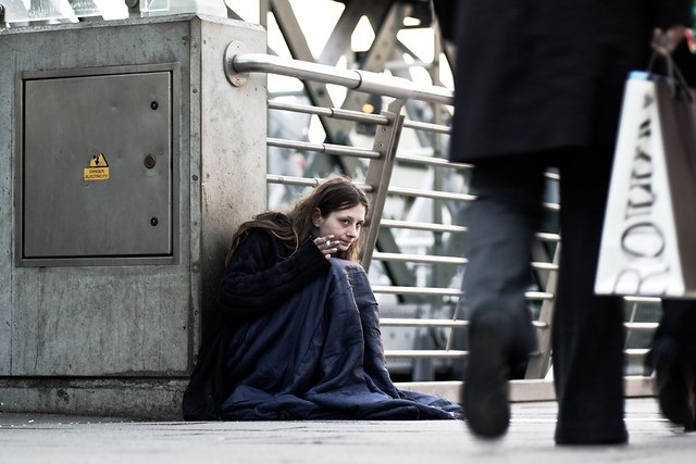 Homeless woman sitting on pavement