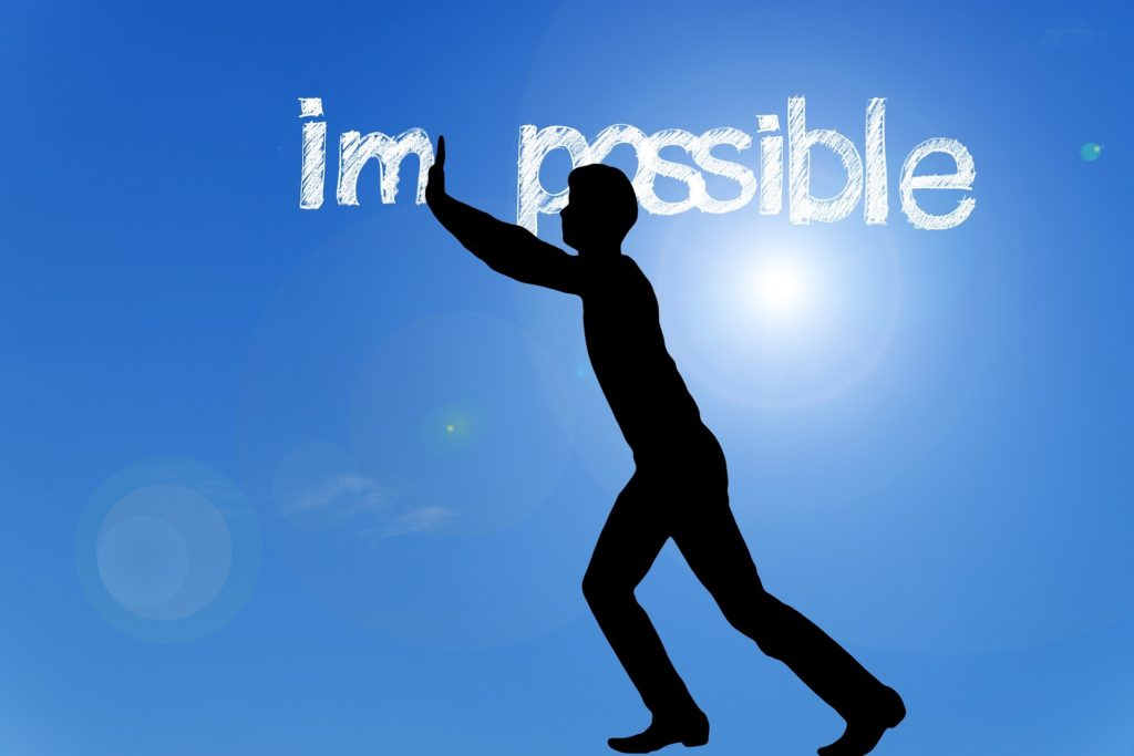 Man pushing the letters im away from the word impossible, leaving the word possible