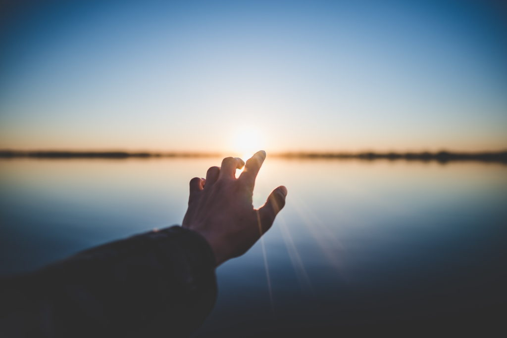 Hand reaching towards the sunrise over a lake