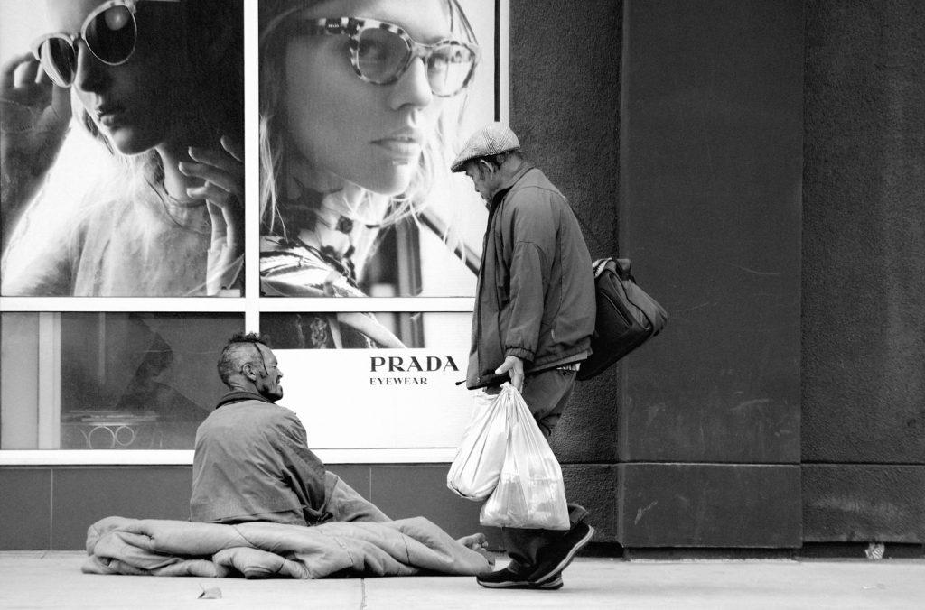 Rough sleeper talking to a shopper outside a Prada shop