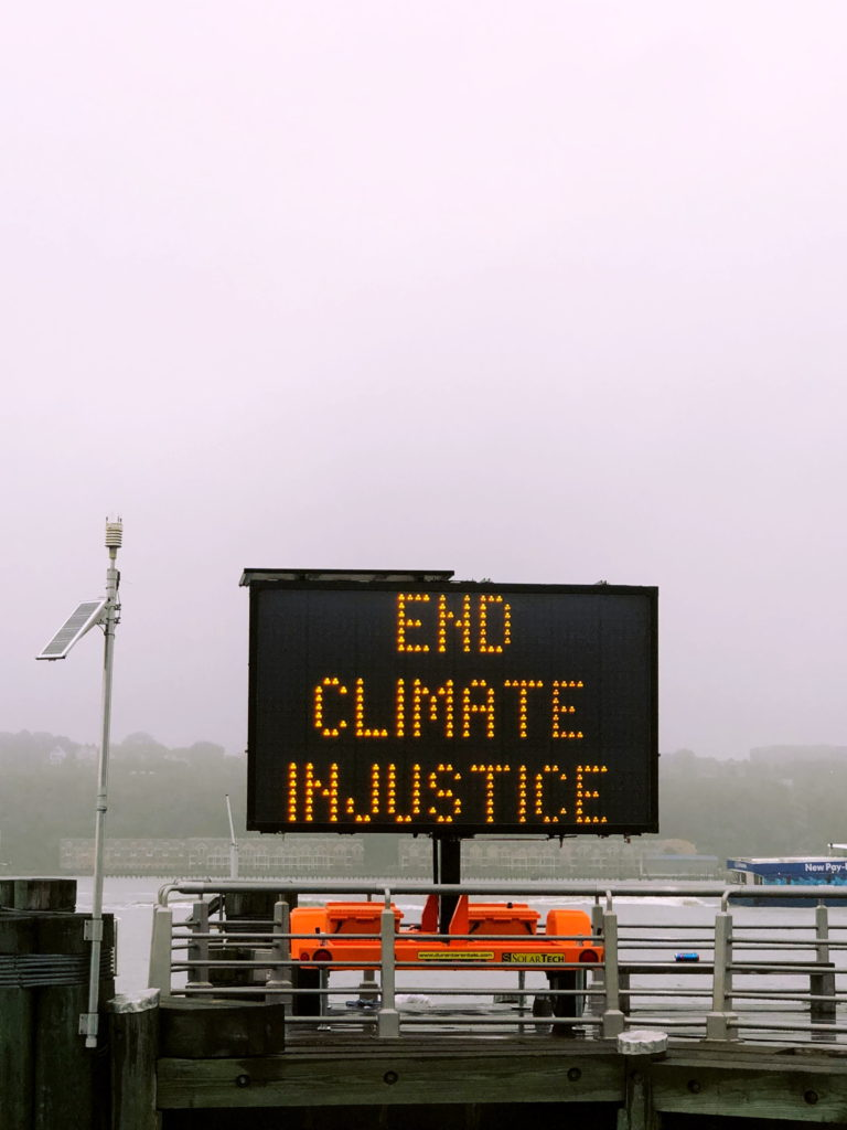 "Electronic sign with the slogan ""End Climate Injustice"" sited by a habour on a cloudy day"