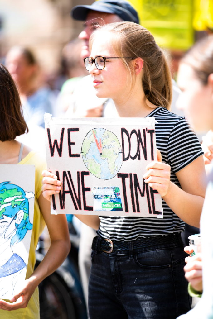 "Climate protester holding sign with the slogan ""We don't have time"""