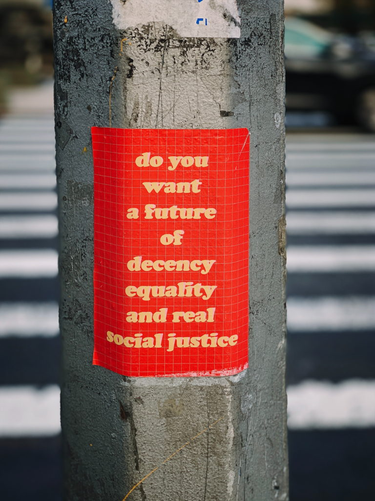 Poster on lamppost with the slogan do you want a future of decency equality and real social justice