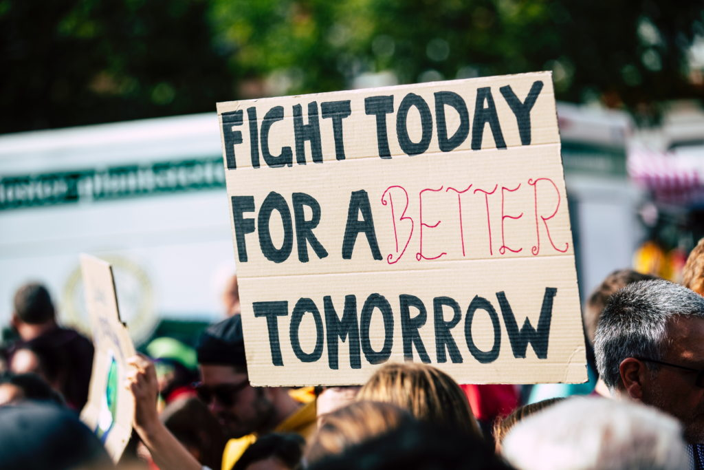 "Cardboard placard at a protest with the slogan ""Fight today for a better tomorrow"""