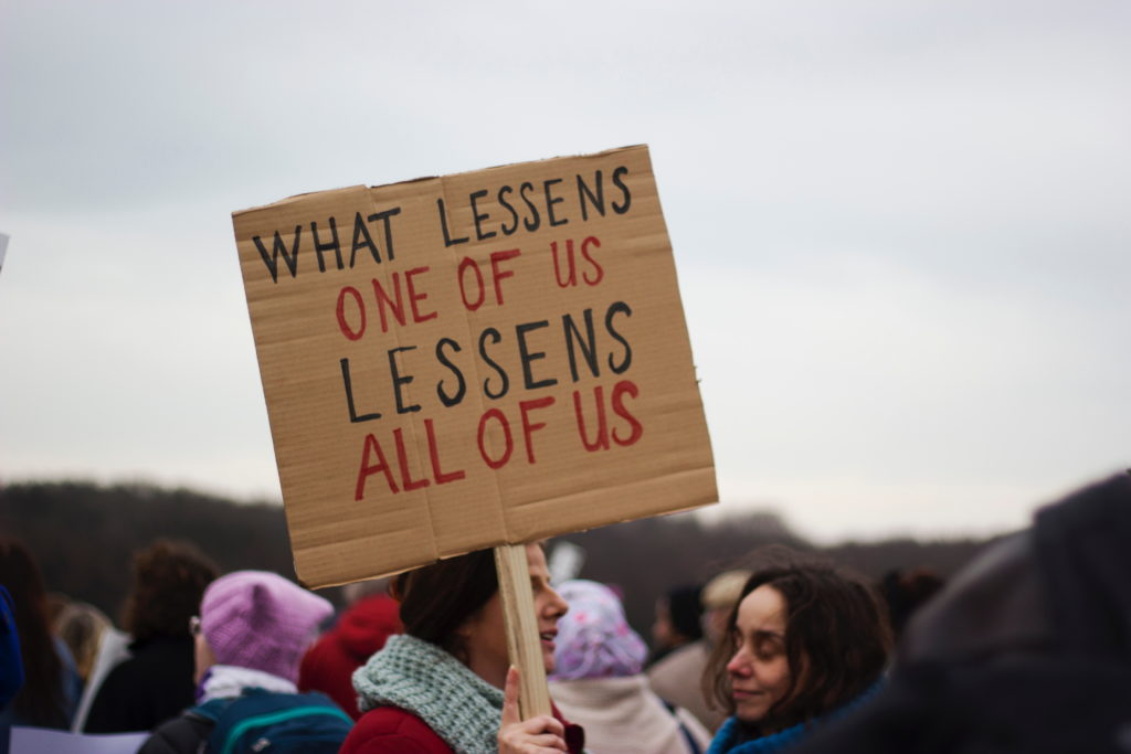"Person at a demonstration holding a placard with slogan ""What lessens one of us lessens all of us"""