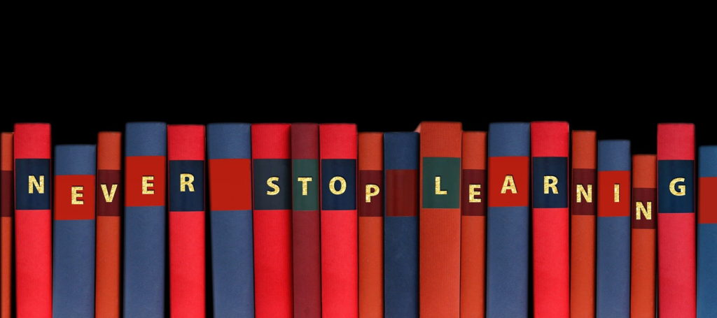 shelf of books with letters on spines spelling the words Never Stop Learning