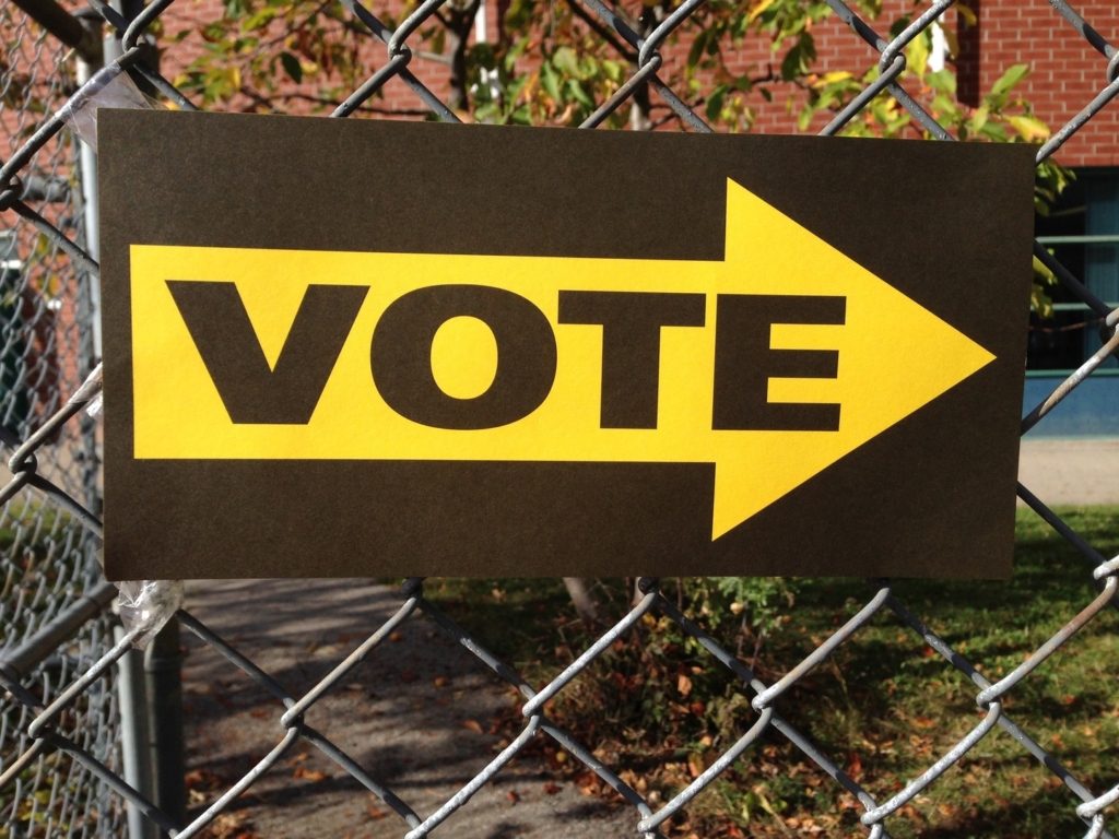 Sign on a fence with and arrow logo and the word vote