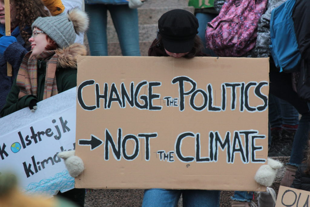 """Protester holding sign with slogan """"Change the politics not the climate"""""""