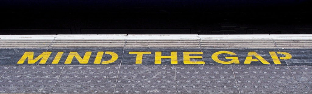 Mind the gap warning painted on a railway station platform