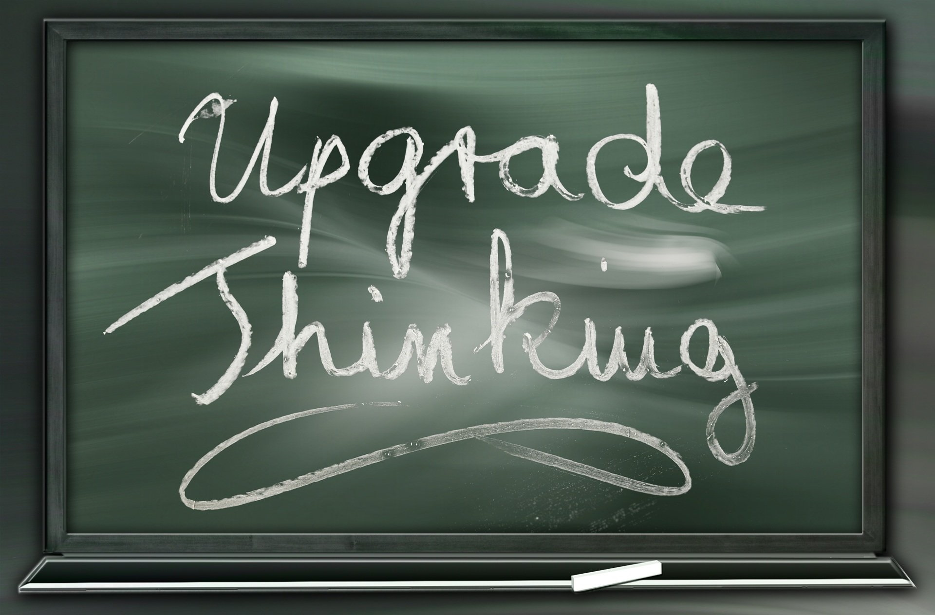 "Blackboard with the slogan ""Upgrade thinking"" written in white chalk"