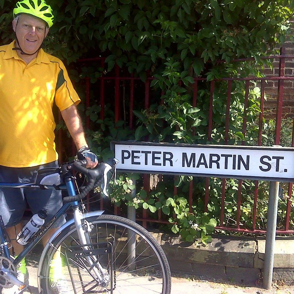 Peter Martin with his bicycle next to a street name sign for Peter Martin Street